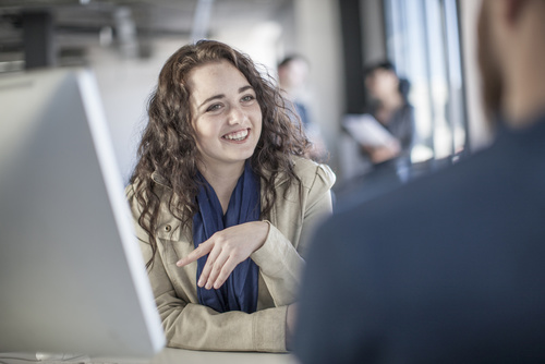 Young woman in office discussing with colleague